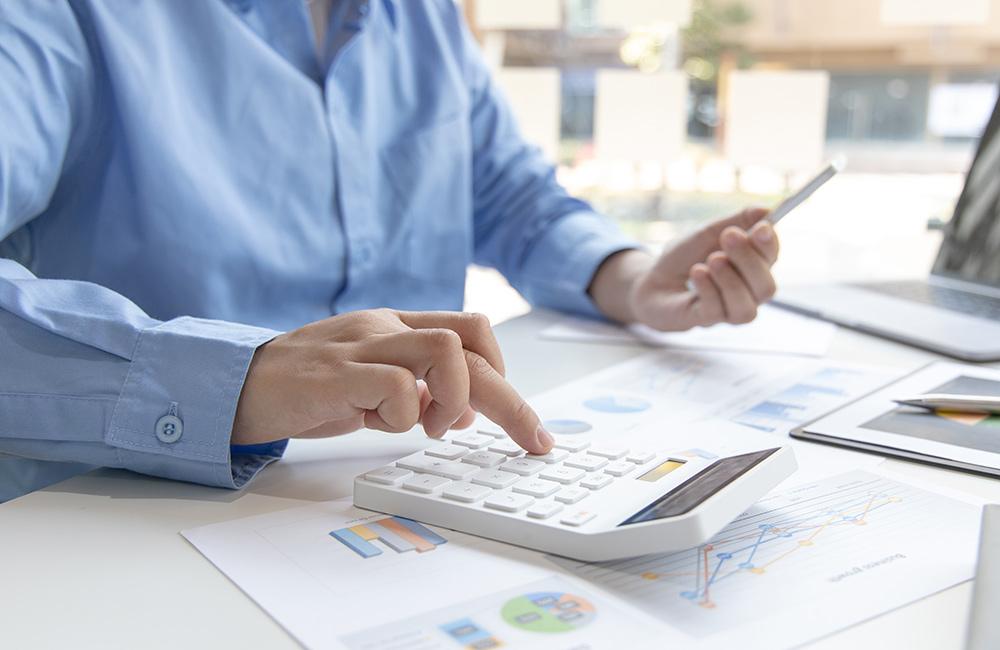 Person i blå skjorta som sitter vid ett skrivbord med en miniräknare i handen och verkar ha full kontroll på kostnader.